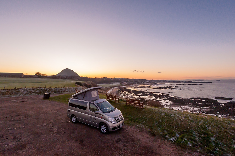 Silver Nissan Elgrand campervan hired from Wee Hoose Campervans in Edinburgh with open pop top roof parked overlooking North Berwick Law in North Berwick Scotland