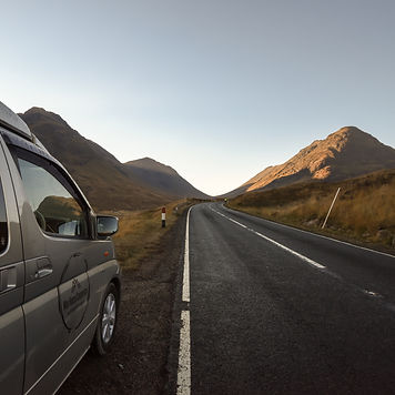VW Campervan in Glen Etive, Glencoe in the Highlands of Scotland looking at Scottish mountains in the summer.