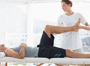 Physiotherapist massaging leg of young m