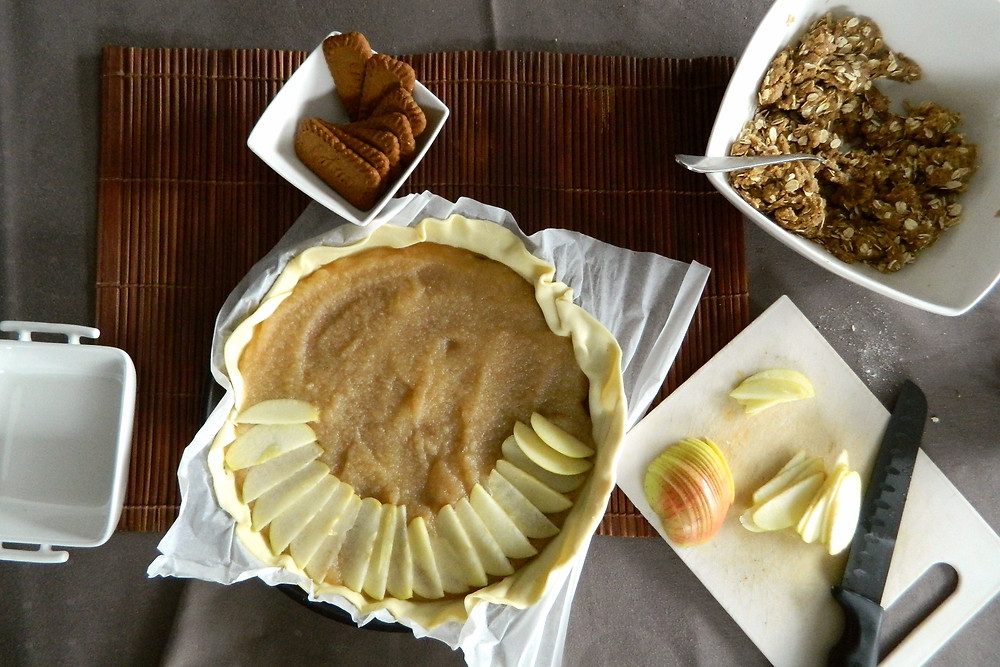 De speculaasbodem bedekt met appelmoes en appelschijfjes.