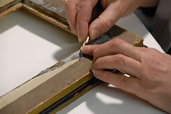 Susie Clark Photographic conservator removing tape from frame