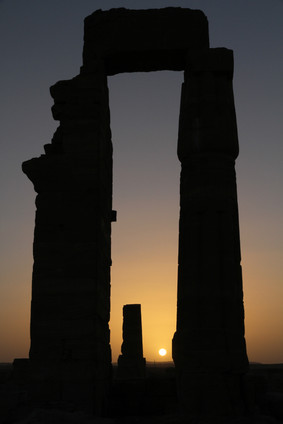 The slowly setting sun outlines the silhouette of a temple gateway