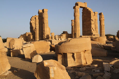 The setting sun casts its soft yellow glow over these majestic temple ruins