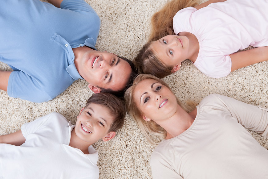 Close-up Of Happy Family Lying On Carpet