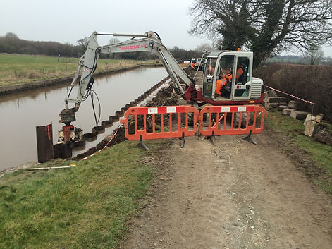 8t digger sat on towpath reaching out in