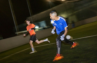 Sports photography:excellent action shot of two soccer players chasing the ball in a night time game.