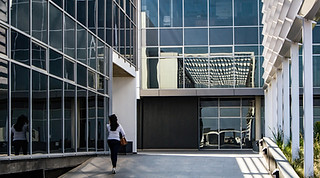 Architecture photography:graphic scene of business woman walking up to a building of glass and metal.
