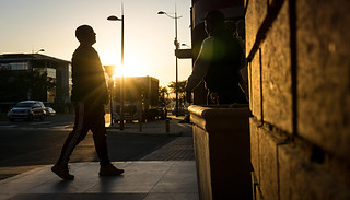Street photography:visually stunning sunset shot of man with head held high on the street.