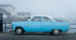 Professional car photography:pale blue vintage car in misty harbour background.