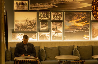 Hotel photography:atmospheric scene of a man in a hotel lounge surrounded by photographs of beach scenes.