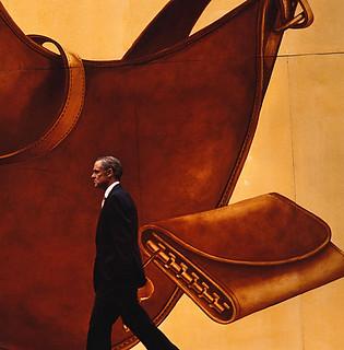 Street photography:elegant man in black suit walking past wall mural of leather handbags.