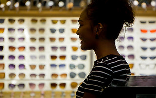 Street photography:colourful graphic image of attractive lady against background of colourful sunglass display.