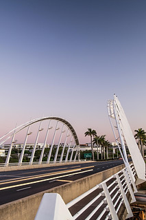 Architectural photography:visually stunning scene of traffic bridge a dusk with a pink and blue sky.