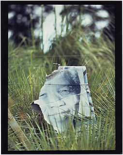 Street photography:Rainwashed election poster on barbed wire fence depicting Nelson Mandela.