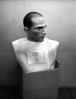Fine art photography:powerful image of male mannequin torso in a cardboard box.