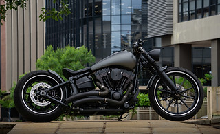 Motorcyle photography:beautiful photograph of custom built motorcycle with buildings in the background in colour.