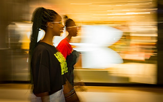 Street photography:very graphic and bright image of two ladies walking through a mall.