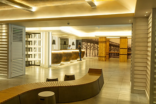 Hotel photography:beautifully lit hotel reception area with person checking in.