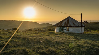 Landscape photography:Beautiful sunrise scene of an African hut with ocean in background.