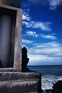 Street photography:graphic scene of sillhouette of fisherman against a dark blue sky.