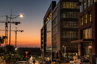 Architectural photography:very rich and dramatic sunset scene of buildings and construction cranes.