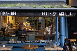 Street photography:atmospheric scene of people in warmly lit coffee shop.