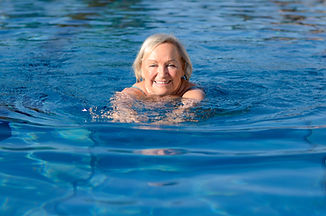 Smiling happy active elderly woman swimm
