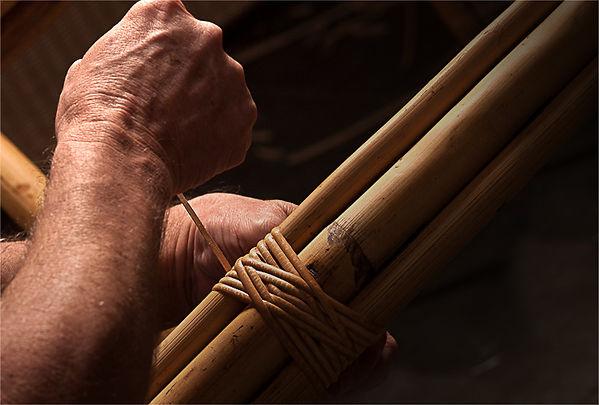 uma mão trabalhando junco, fabricando móveis de junco