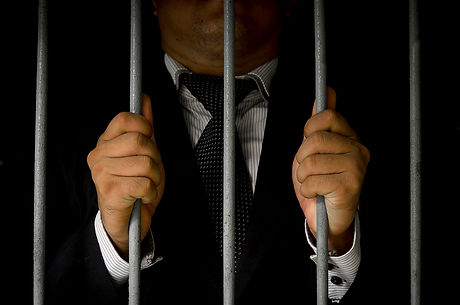 Close-up Of Businessman Hand Holding Metal Bars In Jail with dark environments.jpg