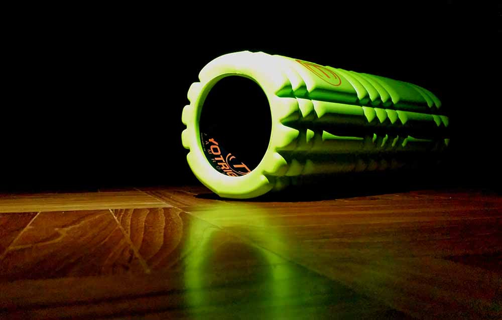 A green foam roller on a shiny wooden floor