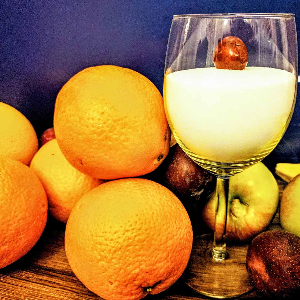 A stack of oranges next to a wine glass half filled with white sugar, with a cherry on top of the sugar in the glass