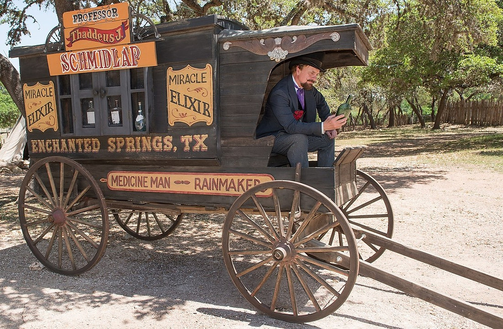 A snake oil salesman, Professor Thaddeus Schmidlap, sits at the front of his horse drawn wagon, admiring a bottle of his miracle elixir