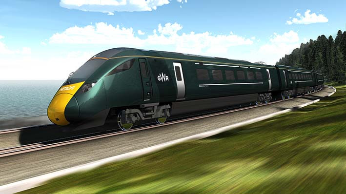 A green GwR train speeds along a track