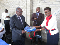 Handover of the Zeebag and a Friendship Bench t-shirt to Dr Kasu by the Project Coordinator Miss Mun