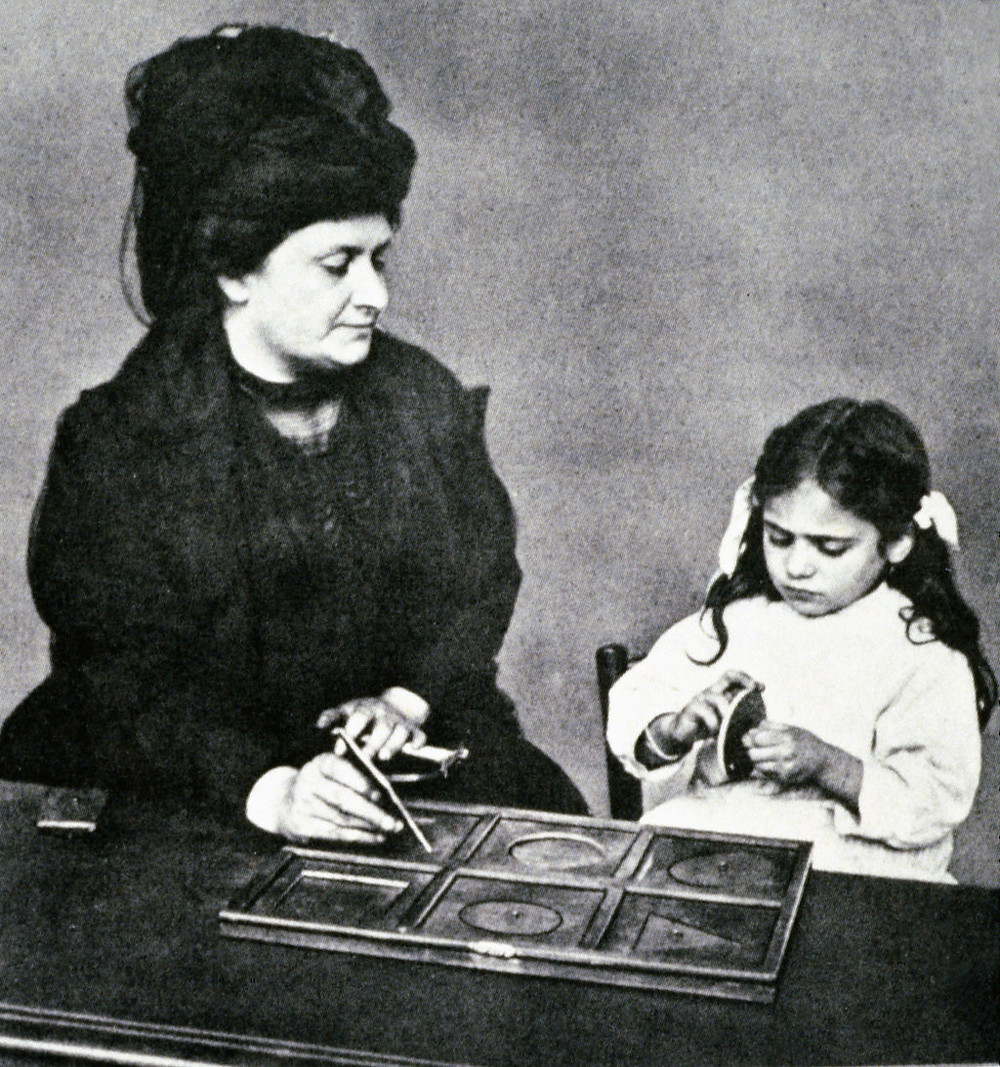 Maria Montessori with young girl playing with geometrical shapes.