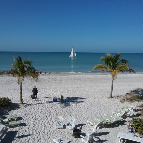 beach view west from bungalows sailboat