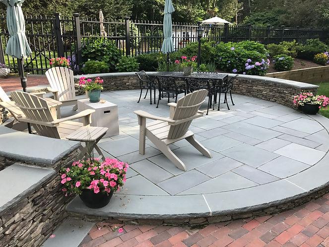 circular stone patio with stone wall in hingam ma