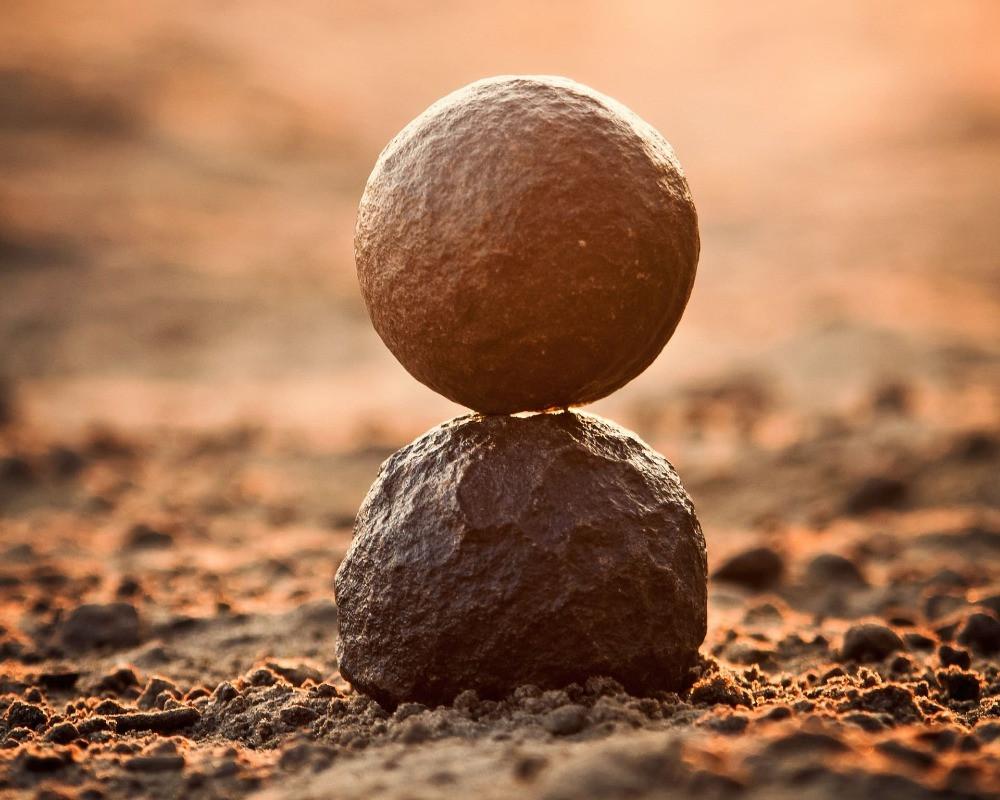 Ziel en ego: een gladde ronde steen op een ruwe ronde steen