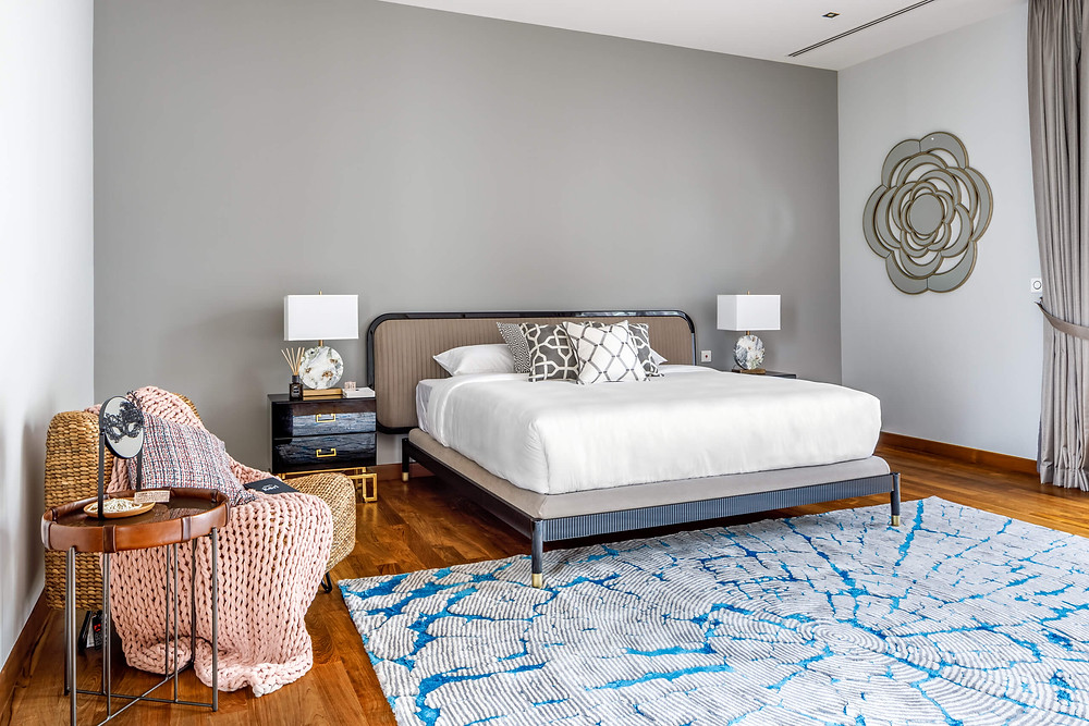 A blue rug adds a pop of colour, in contrast to the earthy palette in the master bedroom
