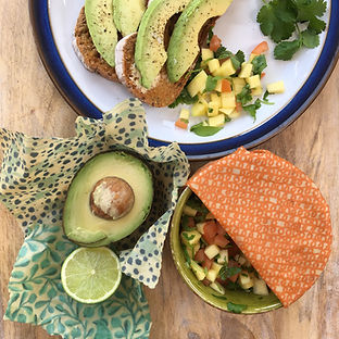 An avocado and lime half being kept fresh in a beeswax wrap.