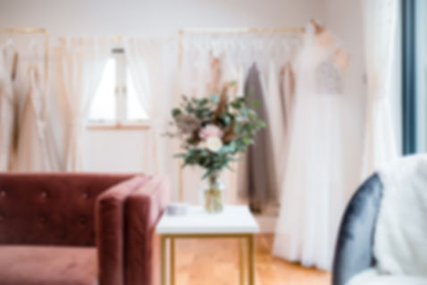 Inside Love in Lace wedding dress shop, Kent. Interior of the shop showing stunning bridal flower display, designer wedding gowns on rails and mannequin.