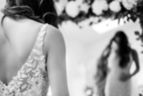 Detail of back of dress as customer looks in the exquisite floral mirror during an exclusive wedding dress appointment at Love in Lace, Kent.
