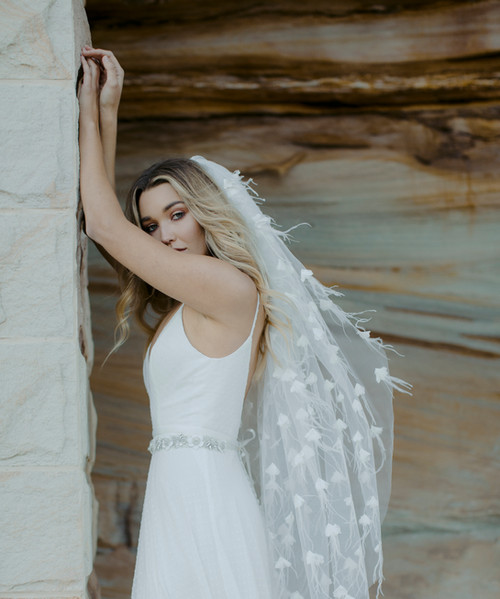 Bride wearing simple wedding dress with floral detail at waist, and intricately feather-detailed bridal veil by Aleksa Karina