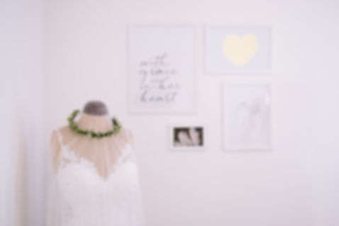 Interior décor at Kent wedding dress shop, Love in Lace. Detail shows bridal gown on mannequin, and framed prints on the walls.