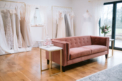 A sneak peek inside Love in Lace, exclusive bridal shop near Chiddingstone, Kent, showing wedding dresses on display and dusky pink modern sofa.