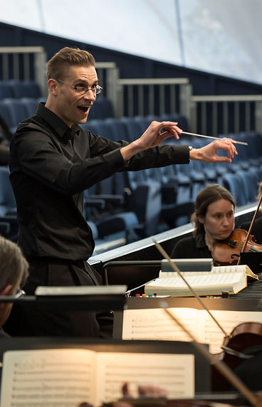 Matthew Kofi Waldren conducts the City of London Sinfonia in rehearsal of Il barbiere di Siviglia at Opera Holland Park in 2014. The leader is Alexandra Wood
