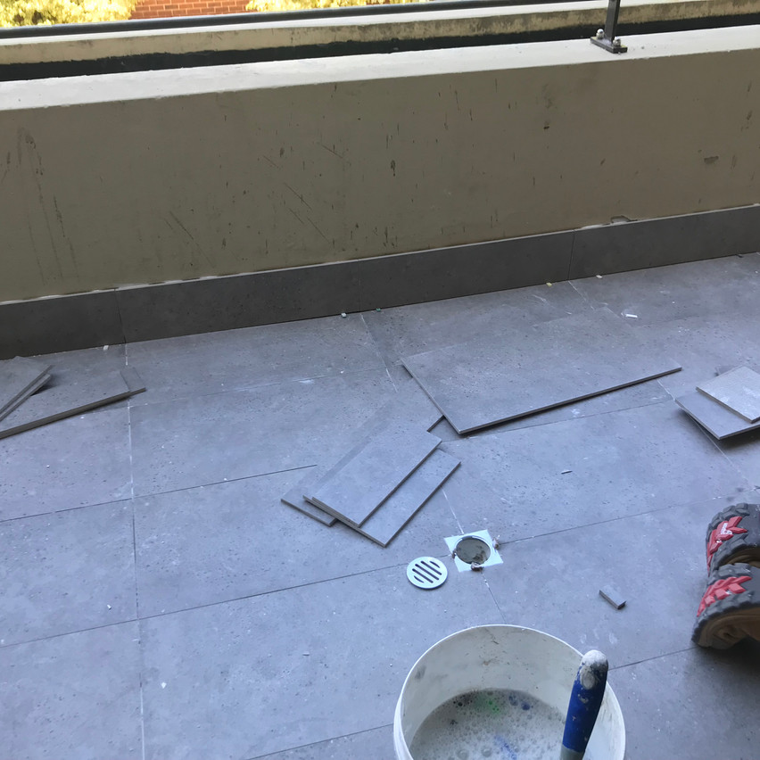 As part of treating the water ingress, the balconies had to have their original tiles and screed removed, new screed installed, a waterproof membrane installed and new tiles put down.