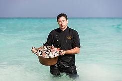 Chef d'un hôtel étoilé debout dans l'océan au Mexique portant une bassine de poisson