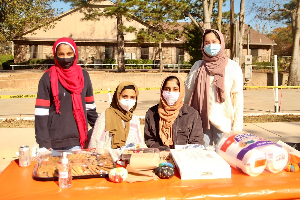 Photo ID: Four teen girls in hijabs sit around a table with cookies and napkins. They are smiling behind branded masks.
