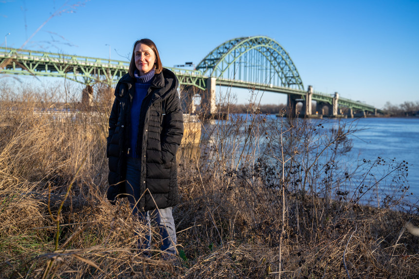 Stephanie Phillips, the executive director of Riverfront North, stands beside a living shoreline along the Delaware River.